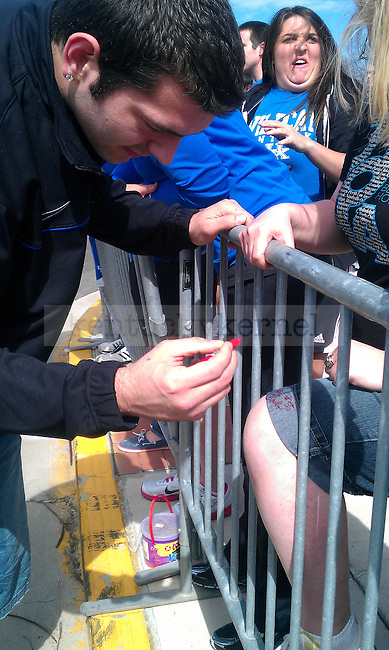 Josh Harrellson signs a pair of jorts outside of Wildcat Lodge in Lexington, Ky., on 4/3/11. Photo by Quianna Lige
