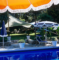 Colourful parasols surround the outdoor swimming pool and the garden is shaded by a length of suspended canvas