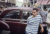 Young man with American car dating from the 1950's in central Havana (Havana Centro).