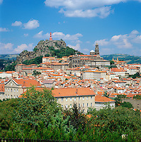 "France, Auvergne (Massif Central), Departement Haute-Loire, Le Puy-en-Velay: view of town with Cathedral of Le Puy, UNESCO World Heritage Site, part of the ""Routes of Santiago de Compostela in France"" and iron statue of Notre-Dame de France (The Virgin Mary) atop the volcanic cone Rocher Corneille 