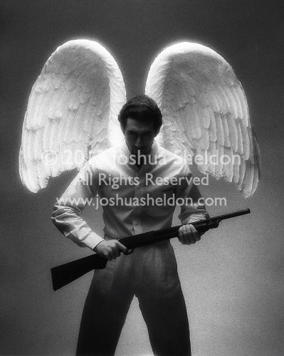 Man wearing angel wings holding shotgun