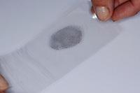 Fingerabdruck, Fingerabdrücke nehmen, um Fingerabdrücke auf einer Fläche sichtbar zu machen, kann man auch Grafit aus Bleistiftminen verwenden, das durchsichtiges Klebeband wird mit dem durch Grafit sichtbar gemachten Fingerabdruck auf eine weiße Pappe geklebt