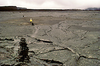 Hiker on the lava field trail to the summit of Mauna Loa with ahu (stone markers) marking the trail