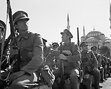 TURKEY, Istanbul, actors in military uniforms holding guns with mosque in the background (B&W)