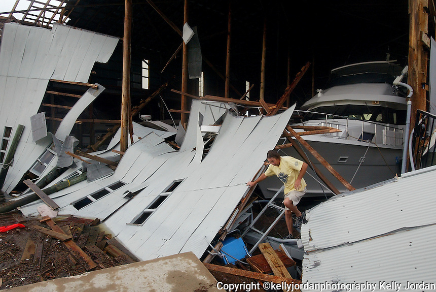 "Kevin Dyke, of Daytona Beach, carefully makes his way through the debris at the Daytona Marina and Boat Works to get from his fishing boat ""Paradise"" to his car parked at the marina. Dyke, who says he stayed at his boat through the storm and also helped to secure other boats throughout the night says his boat is not damaged.(Kelly Jordan)"
