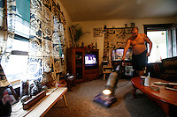 "CHILLICOTHE, MO., 25 SEPTEMBER 2007-  After a weekend of partying, Troy Mantzey cleans the house while his wife works. He says, ""We pretty much split all of the housework, though I do most of the cooking."""