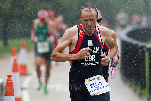 13 SEP 2013 - LONDON, GBR - Ian Gilham (GBR) of Great Britain pushes himself on as he runs through the rain during the ITU 2013 World Age Group Sprint Distance Triathlon Championships  in Hyde Park in London, Great Britain (PHOTO COPYRIGHT © 2013 NIGEL FARROW, ALL RIGHTS RESERVED)