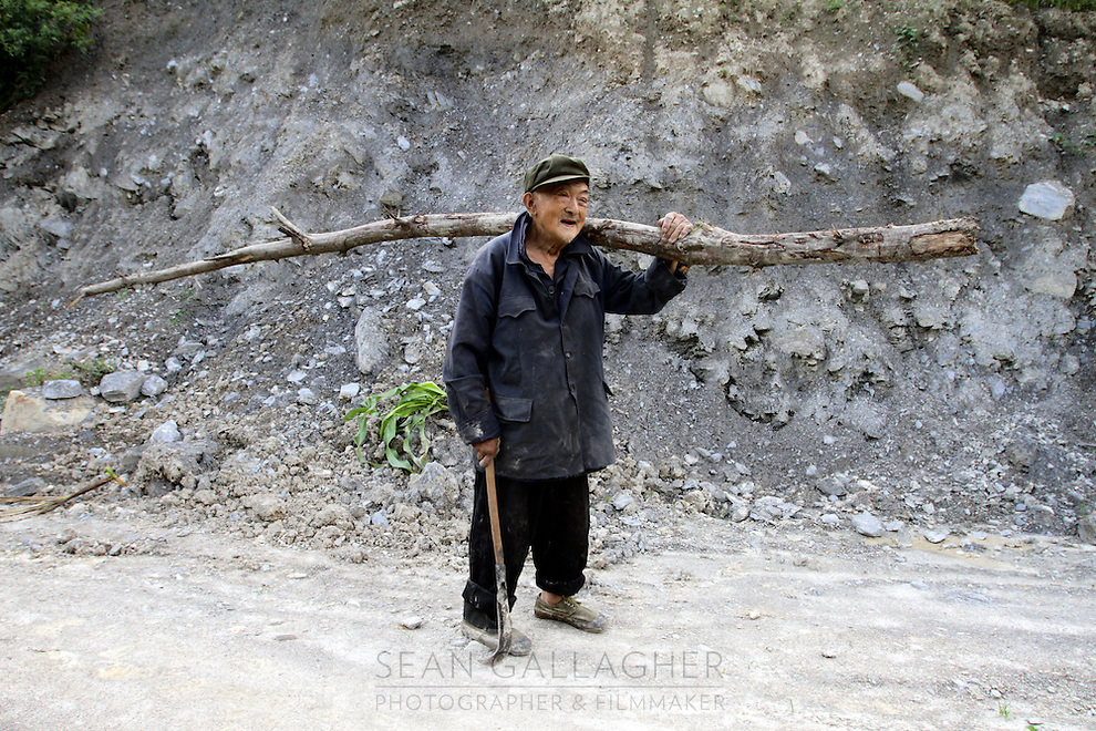 A local man carries a felled tree back to his village in the mountains of northern Sichuan. Pingwu County in Sichuan Province, south-west China.