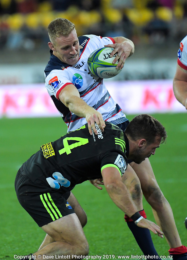 Reece Hodge hands off Wes Goosen during the Super Rugby match between the Hurricanes and Rebels at Westpac Stadium in Wellington, New Zealand on Saturday, 4 May 2019. Photo: Dave Lintott / lintottphoto.co.nz
