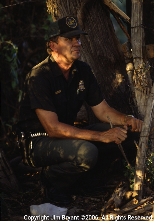 A U.S. Border Patrol Agent in Del Rio, Texas, waits for suspected illegal aliens to cross a field. While the traditional mission of the United States Border Patrol has always been the detection and prevention of the illegal entry of aliens and smuggling of illegal contraband into the United States anywhere other than a designated port-of-entry, the dawn of the age of terrorism within our nation has added a new and high priority mission: to detect and prevent the entry of terrorists and their weapons into the United States. Jim Bryant Photo..©2006. All Rights Reserved.