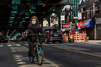 NEW YORK, NY - APRIL 25: A woman wearing a face mask rides her bicycle on April 25, 2020 in Queens, NY. The immigrant community in Queens has been severely affected by COVID-19, the neighborhood is overwhelmed by the number of deaths and infections during recent months, reaching the point of being considered one of the most devastated places by the desease in the U.S. and the world. (Photo by Pablo Monsalve/VIEWpress)