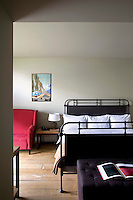 A hotel bedroom is furnished with a simple iron bedstead