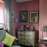 An elaborately painted antique chest-of-drawers is tucked into an alcove by the side of the bed