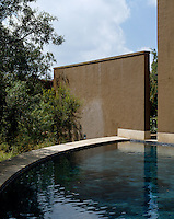 A semi-circular swimming pool is screened by a contemporary adobe-style wall