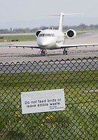 Sign at Manchester Airport's Viewing Park reading 'Birds are a Hazard to Aircraft. Do not feed birds or leave edible waste' with an aircraft behind a wire fence.