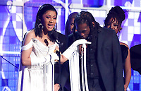 "Cardi B, left, accepts the award for best rap album for ""Invasion of Privacy"" as Offset kisses her hand at the 61st annual Grammy Awards on Sunday, Feb. 10, 2019, in Los Angeles. (Photo by Matt Sayles/Invision/AP)"