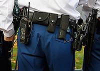 Politie met riem waaraan oa  handboeien en een revolver hangen