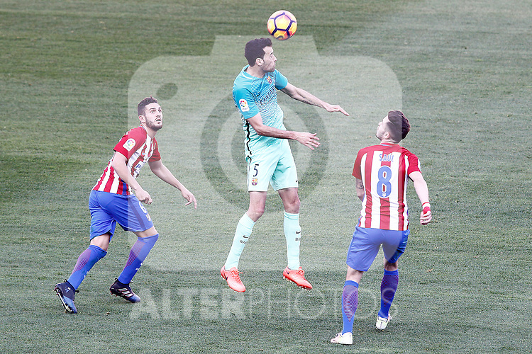 Atletico de Madrid's Koke Resurrecccion (l) and Saul Niguez (r) and FC Barcelona's Sergio Busquets during La Liga match. February 26,2017. (ALTERPHOTOS/Acero)