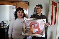 Gao Cuilan (gauche) et Li Fang (droite) montrent leur nouvelle photo de mariage, à Baoshan, près de Shanghai, le 7 mai 2008. Ils se sont mariés pendant les années 70, mais à l'époque, le souvenir était consigné en un minuscule cliché strict en noir et blanc, les mariés en costumes de « camarades »... et, comme bien des couples, ils le regrettent. Il est de la dernière mode dans les grandes villes de poser en studio en costumes et mise en pli pour une nouvelle photo de couple. « C'est notre fils qui nous a poussé à la faire », raconte Li Fang. Et comme la plupart des Chinois qui viennent de s'enrichir, Li Fang et Gao Cuilan n'enlèvent pas les coins protégeant les cadres. Photo par Lucas Schifres/Pictobank