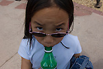 Chinese-American girl drinking soda with a sad look