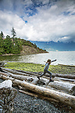 CANADA, Vancouver, British Columbia, young girl walks on driftwood logs at Brigade Bay on Gambier Island, in the Howe Sound with the Britannia Range in the distance