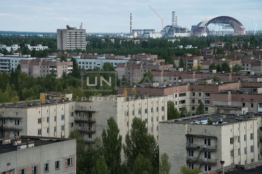 Chernobyl power plant and the raising Arch seen through abandoned Prypyat city. Once a modern and beautiful -by Soviet standards- today it is a ghost town