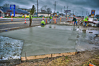 Construction workers struggle to finish a the concrete driveway into a shopping center to beat the forecast of heavy rains later in the day. Construction along Westerville Road has been plagued by poor weather as the  first  section of work nears an end.wider lanes and an improved traffic pattern.