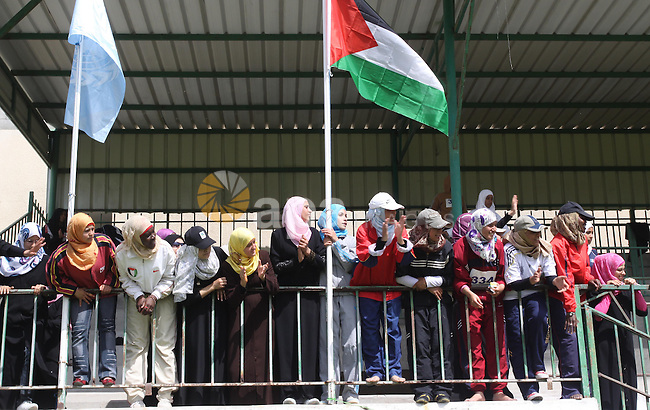 Palestinian girls cheer for women athletes, not seen, during a local athletics competition at Palestine Stadium in Gaza City on May 8, 2010. Photo by Mohammed Asad