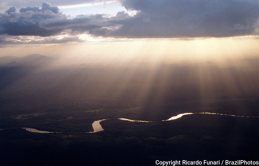 Aerial view of sinuous river in Amazon rain forest, solar rays through clouds at susnset, Brazil.