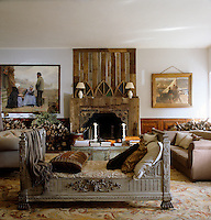 A distressed wooden daybed in front of a gothic-inspired chimneypiece in the main living room which is flanked by piles of logs and kindling and 19th century Breton paintings