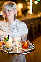 Waitress/bartender Carla Wolff delivers a tray of drinks (the Champ, corpse reviver, and a negroni) at Fox Liquor Bar in Raleigh, NC.