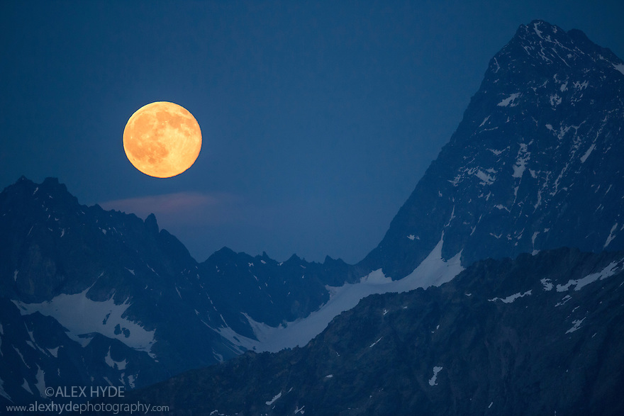 Full moon rising between the Verpeilspitze (3430m, left) and the Watzespitze (3554m, right). These peaks are part of the Glockturmkamm, the westernmost ridge of the Otztal Alps. Nordtirol, Austrian Alps. July. Digitally stitched panorama.