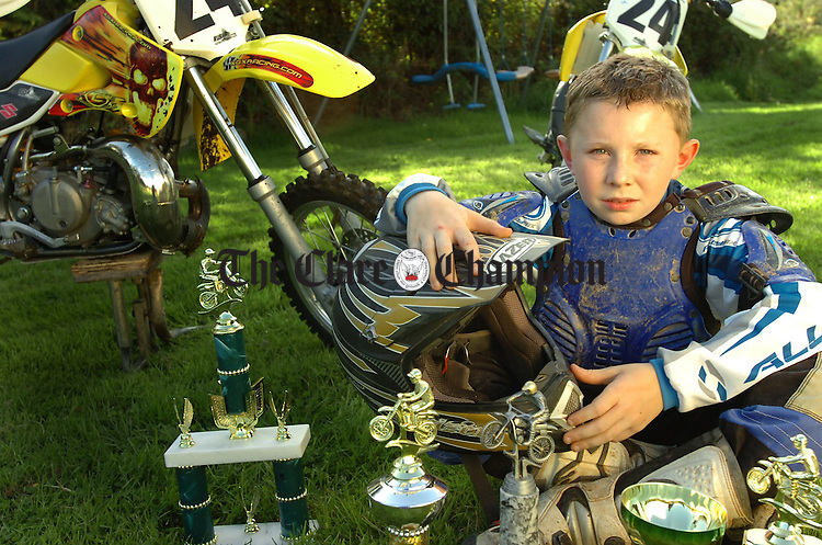 11 year old MotoX biker John Cullinan from Barefield Ennis pictured with his bikes a selection of the trophies he has won.Pic Arthur Ellis.