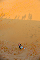 7 year old child with plastic sled, after sliding to bottom of large sand dune. Red Sand Dunes, Mui Ne, Vietnam