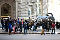 Tourists photograph the famous Wall Street Bull on Saturday, April 5, 2014, in New York. (Photo by James Brosher)