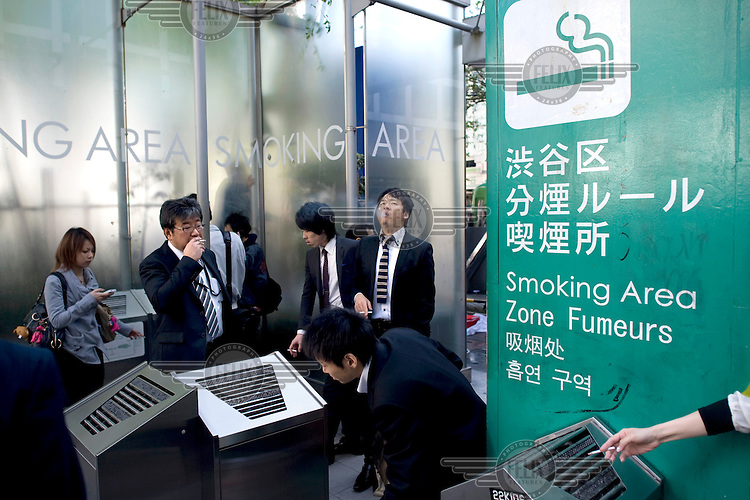 Businessmen and women smoking in a designated smoking area in Shibuya. /Felix Features
