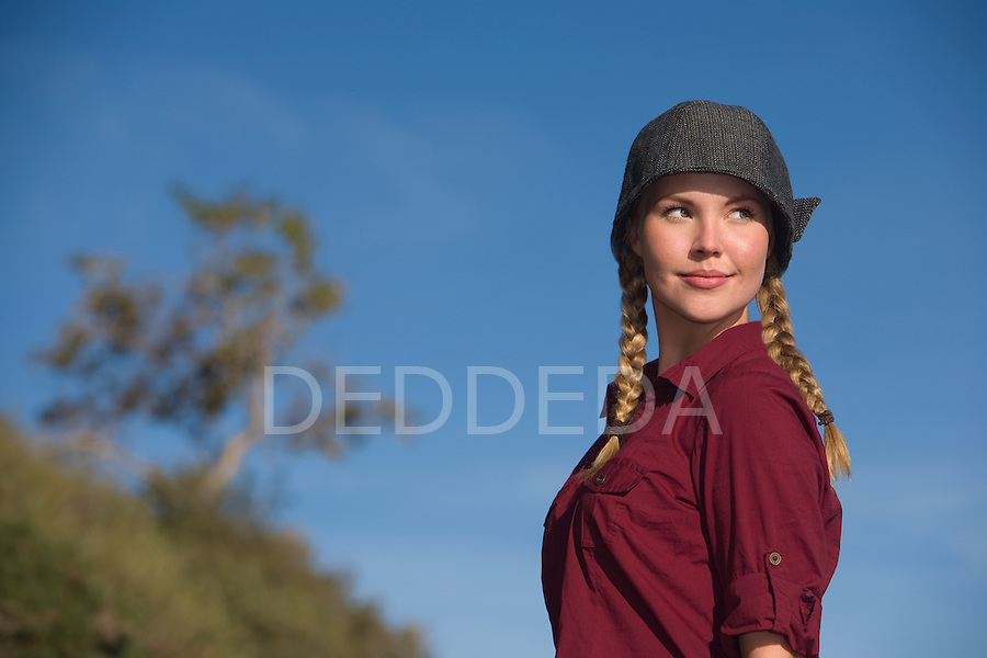 Pretty young blond woman with braided hair wears a fashionable hat outdoors.