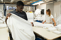 Allan Baxter, 40, (left) and Stela Poparova, 24, work in the laundry of the Harborside Inn in Edgartown, Martha's Vineyard, Massachusetts, USA. From St. Mary Parish, Jamaica, Baxter has worked at the hotel on an H2B visa for seasonal foreign workers. He spent last winter working in Stowe, Vermont, as well. The hotel has had difficulty this year getting as many H2B visas as it had in previous years. As a result, Baxter is the only person working in the laundry room on most days; it was a two-person job last year. Workers from other areas of the hotel, like Poparova, who is officially employed as a pool attendant, sometimes work short shifts in the laundry room to help Baxter. Poparova is from Plovdiv, Bulgaria, and has a J1 visa for students. She is a linguisitics student at New Bulgarian University in Sofia, Bulgaria.