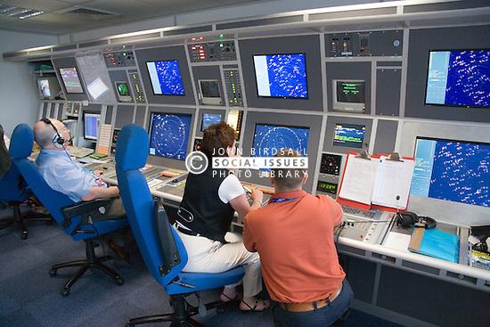 Air Traffic Control Tower Operators watching radar screens at East Midlands Airport,