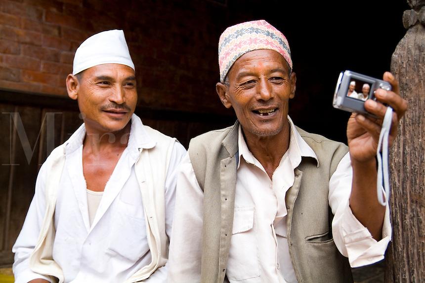 Hindu men take a picture with digital camera self portrait in village of Bhaktapur a town near Kathmandu Nepal