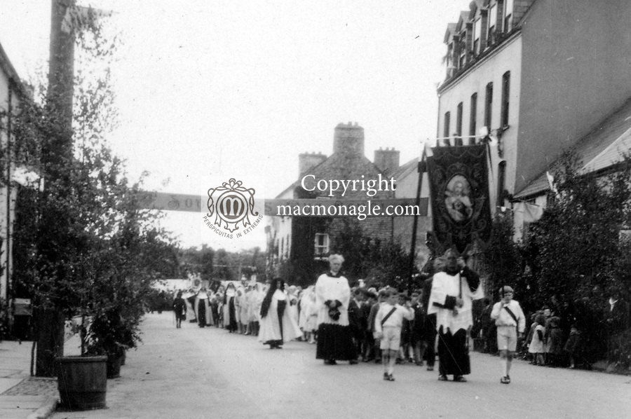 The Corpus Christi procession in 1930 coming down High Street, Kilarney, in front are Brother Juniper, OFM with banner, Sean and Donal macMonagle holding the banner ribbons, Fr Denis Moynihan, curate and later Bishop of Kerry..Photo by Daniel macMonagle..captioned by Paddy macMonagle