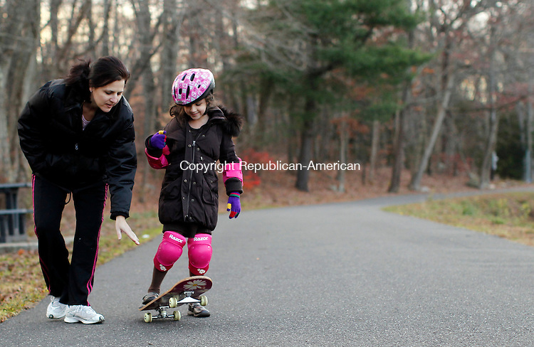 Naugatuck, CT- 14, November 2010-111410CM08 Tracy Mariano (left) coaches her daughter Julia, 8, of Naugatuck how to ride a skateboard Sunday afternoon at Baummer Pond in Naugatuck.  It was Julia's second time out on a skateboard. According to the national weather service, today is supposed to be mostly cloudy, with areas of drizzle in the morning. The high's are expected to be in the lower 50's.   Christopher Massa Republican-American