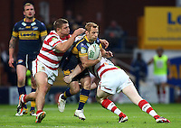 PICTURE BY VAUGHN RIDLEY/SWPIX.COM - Rugby League - Super League - Leeds Rhinos v Wigan Warriors - Headingley, Leeds, England - 01/06/12 - Leeds Rob Burrow is tackled by Wigan's Michael McIllorum and Liam Farrell.
