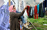 """A woman refugee from Syria puts her laundry out to dry. She lives with her family in a rented """"tent""""--made from a billboard canvas--in the village of Jeb Jennine, in Lebanon's Bekaa Valley. They and other refugee families in the area are being assisted by International Orthodox Christian Charities and other members of the ACT Alliance.."""