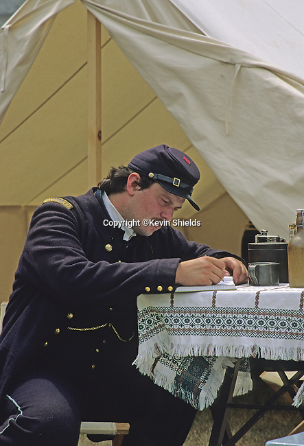 A re-enactor portraying a US Civil War soldier writing in a book at a  field camp at Fort Knox State Park in Prospect, Maine, USA, July, 1991.