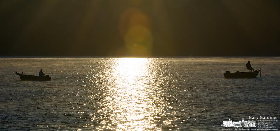 Fishermen on lake at sunrise in light fog