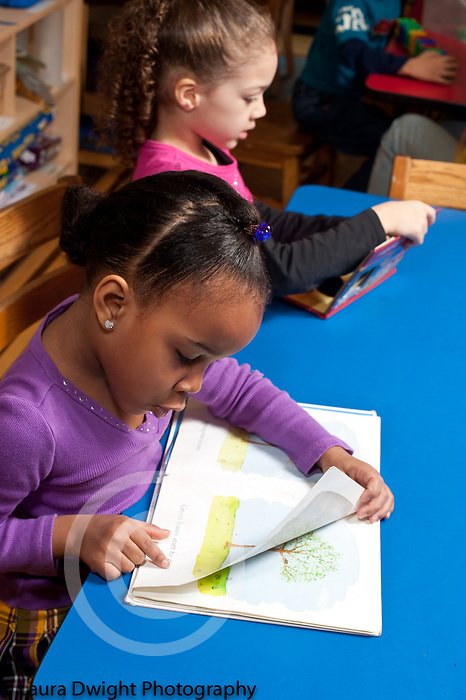 Education preschool two girls sitting side by side at table, one looking at picture book and either telling herself the story or sounding out words, the other looking at book
