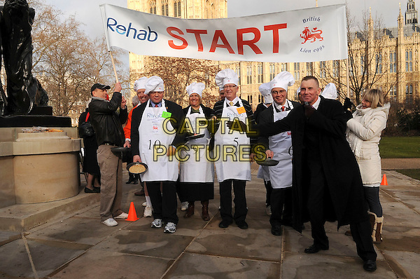LORD ADDINGTON, LORD McNALLY, BRIAN IDDON, GARY GIBBON & GARY RHODES.The annual Parliamentary Pancake Race in front of Houses of Parliament, London, England. .February 9th, 2010.full length apron chef hat food frying pan black flip flipping start arms outstretched .CAP/IA.©Ian Allis/Capital Pictures.