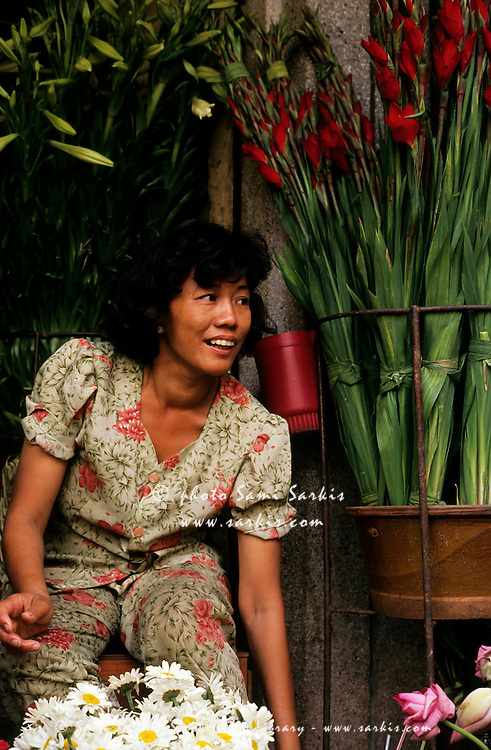 Portrait of a woman smiling while selling bunches of flowers.