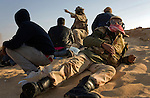 Rebels take cover from shelling behind a sand dune near the city of Ajdabiya, Libya, March 24, 2011. Despite air strikes from Western war planes, which crippled Col. Muammar Qaddafi's military capability, the rebels seemed unable to advance and retake the city.
